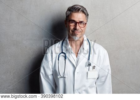 Portrait of trustworthy older smart doctor with gray hair wearing glasses and white lab coat standing against gray wall, smiling. Copy space.
