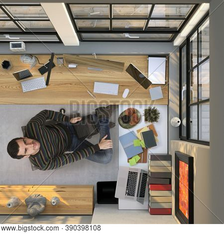 Man working at home in homeoffice with computer, looking up, above the head view of study room.