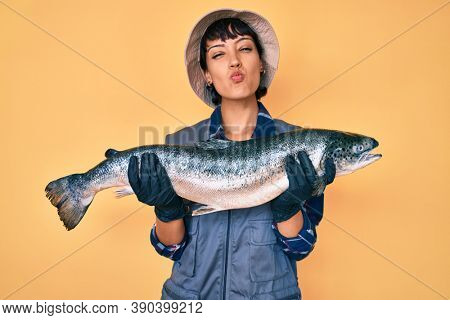 Beautiful brunettte fisher woman showing raw salmon looking at the camera blowing a kiss being lovely and sexy. love expression.
