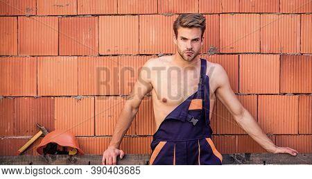 Sexy Laborer. Attractive Worker. Handsome Man Wear Overalls. Construction. Worker Brick Wall Backgro