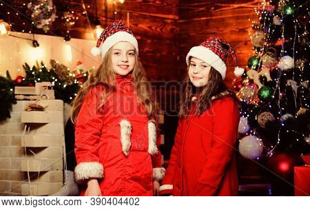 Little Girl Sisters In Red Hats. We Are Family. Elf Children. Xmas Tree Decoration. Santa Claus Litt