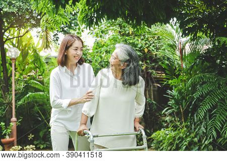 Daughter Caring For Elderly Asian Mother Come Take A Walk In The Garden With Fresh Green Plants. Mak