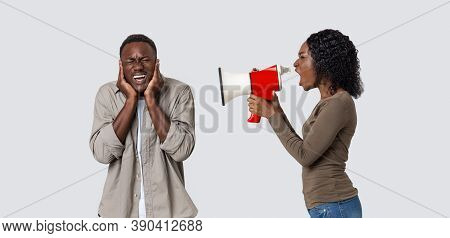 Misunderstanding In Couple, Marriage, Family. Furious Black Woman Shouting Through Megaphone At Her