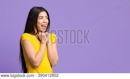 Excited Asian Female Looking At Copy Space And Exclaiming With Excitement, Clenching Fists In Happy