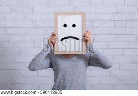 Depression, Sadness, Negative Emotions Concept. Young Woman Holding Picture Frame With Sad Emoticon