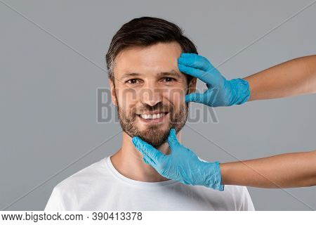 Cosmetician Hands In Protective Medical Gloves Touching Smiling Man Face Over Grey Studio Background