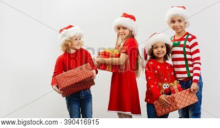 A Group Of Happy Children With Christmas Gifts In Their Hands And In Holiday Costumes On A White Bac