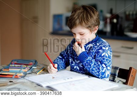 Lonely School Kid Boy At Home Making Homework. Little Child Writing With Colorful Pencils, Indoors.