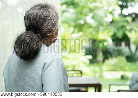 A Sad Old Elderly Woman Uses Walker For Standing In Front Of Windows And Looking Outside And Feeling