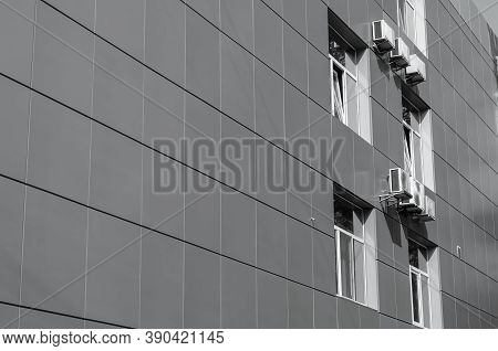 Metal Exterior Siding Of A Building. Wall Of A Corporate Building With Windows And Air Conditioning.