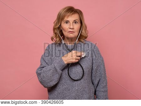Young Mature Female Woman Looking Surprised When Checking Her Heart With Stetoscope