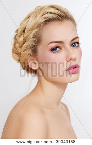 Young beautiful healthy blond girl with braids and clear make-up on white background