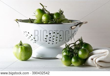 Unripe Green Tomatoes In Colander And On Table In White Wooden Kitchen Background, Unripe Tomatoes C