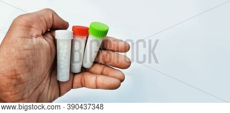 Homeopathic Medicines In Small Bottles Hold In Hands In White Background