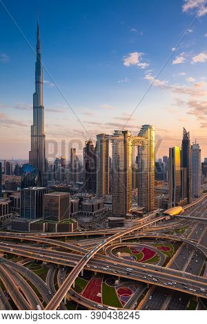 The Futuristic View Of Dubai Skyline At Dusk With Sheikh Zayed Road And Dubai Metro On The Foregroun