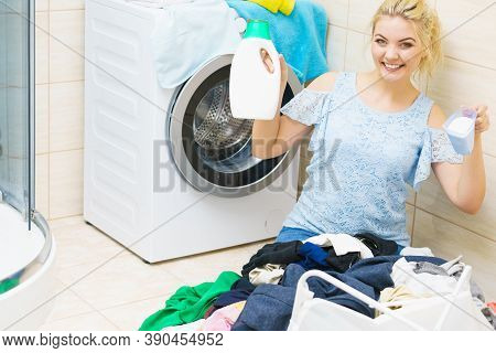 Young Woman Sitting In Bathroom Sorting Clothes Into Washing Machine. Female Doing Dark Laundry Hold