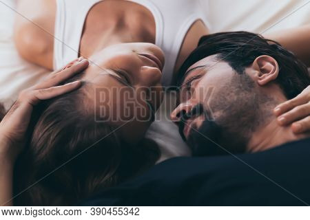 Close Up Couple In Love. Beautiful Woman And Handsome Man Laying Down On Bed And Touching Each Other