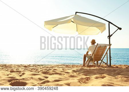Man Relaxing On Deck Chair At Sandy Beach. Summer Vacation