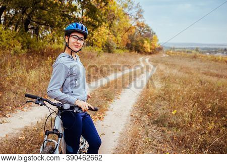 Riding Bicycle In Autumn Field. Young Woman Having Rest After Workout On Bike Enjoying Nature. Healt