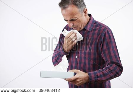 Studio Shot Of Mature Man With Cold Or Flu Virus Sneezing Into Paper Tissue Agaisnt White Background
