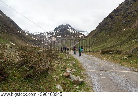 Group Of People Hiking And Mountain Snow Panorama In Tyrol Alps, Austria