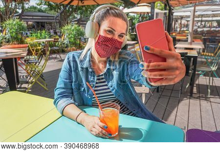 Fashionable Young Woman Influencer Taking Selfie Outdoor While Wearing Protective Face Mask