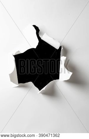 Ripped Hole In White Paper With Black Background Inside