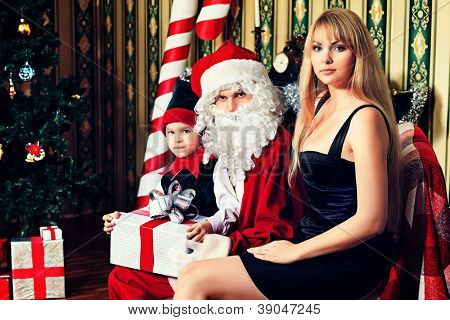 Portrait of a happy family spending Christmas time with Santa Claus at home.