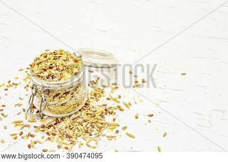 Mix Of Variety Of Cereals In Glass Jar On Black Stone Background