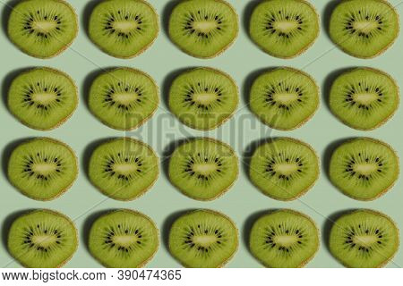 Kiwi Pattern. Repetition Of Kiwi Slices On A Light Green Background. Colorful Food Background. Fruit