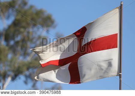 English Flag Flying On Flagpole On Blue Sky Background