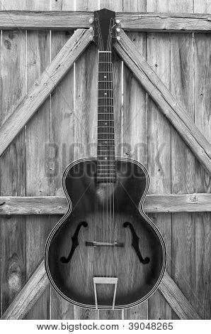 Monochrome Vintage Acoustic Guitar On Fence