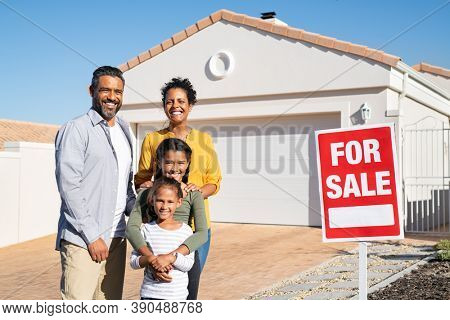 Happy mixed race family standing outside home with sale signboard. Couple with two daughters standing by for sale sign outside their new house while looking at camera, put the house up for sale.