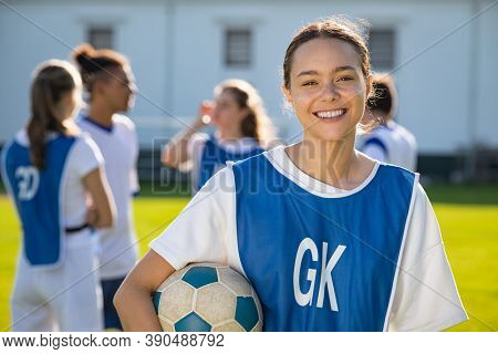 Cheerful soccer player holding a football and looking at camera. Portrait of young woman during training on soccer field. Satisfied high school student with her teammates standing in background.