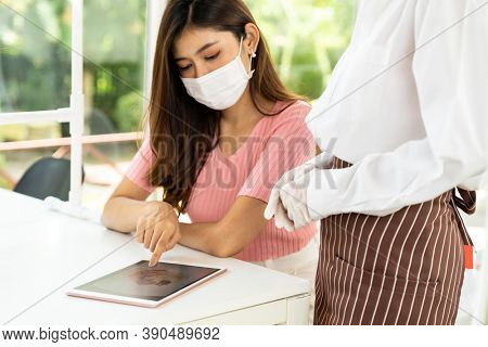 Asian waitress wear facemask and face shield using tablet to show restaurant electronic menu and recommend to customer. New normal technology and lifestyle food and dining concept.