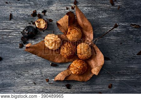 high angle view of some different panellets, typical confection of Catalonia, Spain, eaten traditionally in All Saints Day, on a dry leaf placed a rustic gray wooden table next to a roasted chestnut