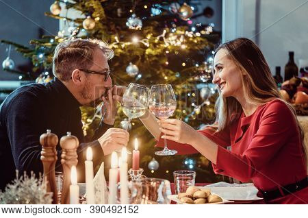 Middle aged couple drinking wine on Christmas eve in front of brightly lit tree