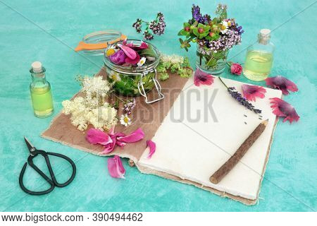 Naturopathic herbal medicine with summer flowers & herbs loose & steeping in a jar with oils for aromatherapy essential oil. Still life with old hemp notebook & rustic pencil. Natural health care.
