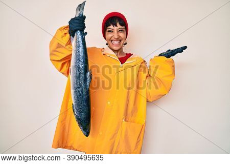 Beautiful brunettte fisher woman wearing raincoat holding fresh salmon celebrating victory with happy smile and winner expression with raised hands