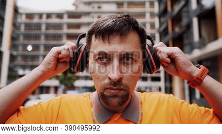 Construction Worker With Ear Muff Working At Construction Site. Worker Puts On Ear Defenders To Prot