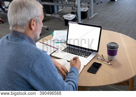 Senior Caucasian businessman in a modern office, sitting at table using laptop computer for online meeing and writing notes. Social distancing in workplace during Coronavirus Covid 19 pandemic.