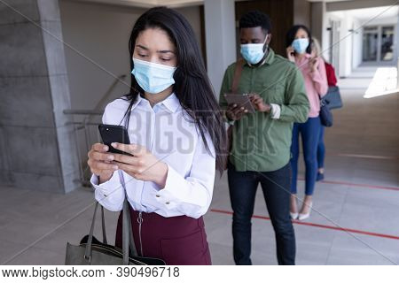 Multi ethnic group of male and female coworkers wearing face masks waiting for health check before entering office. Hygiene and social distancing in workplace during Coronavirus Covid 19 pandemic.