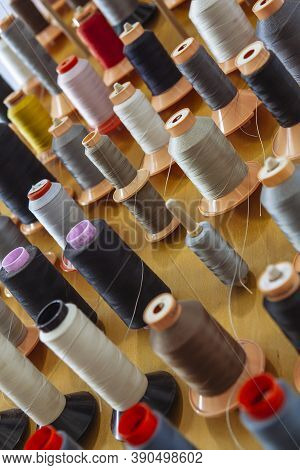 Many Spools Of Multicoloured Threads For Clothes Manufacturing.