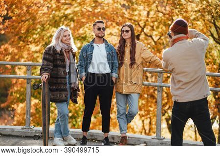 Carefree And Well Dressed Company Of Two Guys And Two Girls Having A Good Time And Photographing In