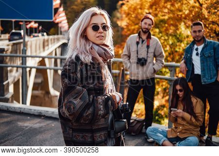 Well Dressed Beautiful Blond Posing With Camera Staying In Foreground In Background Of Autumn Nature