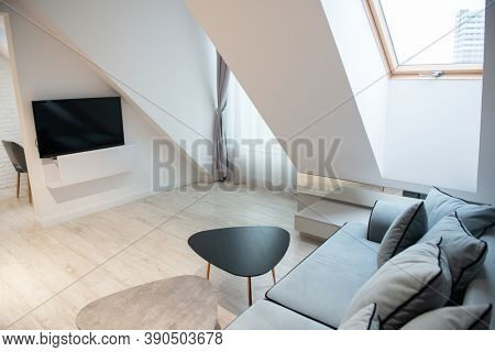 Modern design home interior of studio living room and kitchen in mansard with sofa and elegant accessories. Stylish home decor