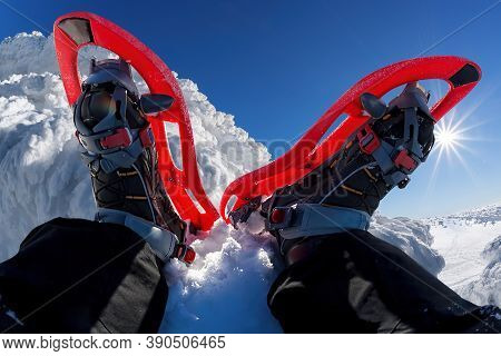 Red Snowshoes Against Beautiful Winter Rocky Mountains