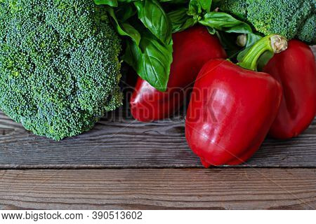 Seasonal Raw Ripe Vegetables Green Broccoli, Red Bell Pepper And Fresh Green Basil On Wooden Backgro