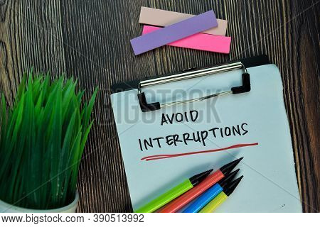 Avoid Interruptions Write On A Paperwork Isolated On Wooden Table. Motivation Or Insipiration Concep