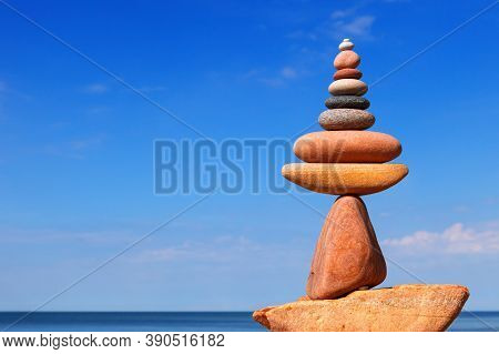 A Bright Rock Zen Pyramid Of Pink Pebbles Against A Blue Sky. Concept Of Life Balance, Harmony And M